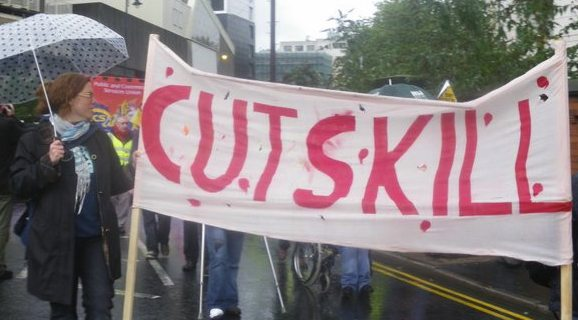 Banner with 'cuts kill' painted on in red